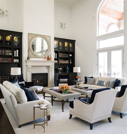 In the family room, plush sofas from Swaim flank coffee table/ottomans by Hickory Chair.