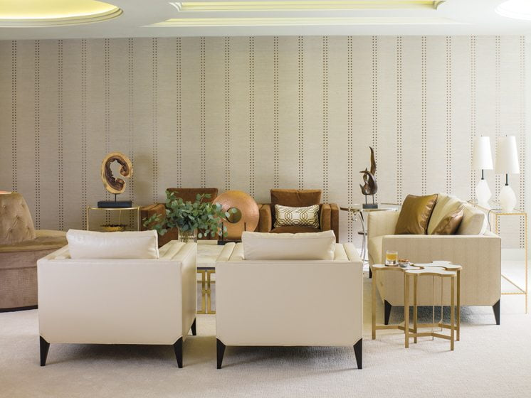 Ceiling cut-outs define the seating area, where a grass-cloth Phillip Jeffries wall covering is a graphic backdrop.