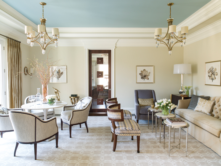 Currey & Co. chandeliers provide sparkle in the living room, where a sofa and lounge chair are by Kravet.