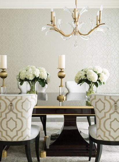 Glamorous touches grace the dining room, from a walnut table designed by Halewski to a gold-leaf chandelier.