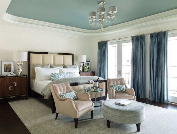 The master bedroom is a picture of serenity with luxurious silk drapes, a Kravet ottoman and bedding from Valerianne.
