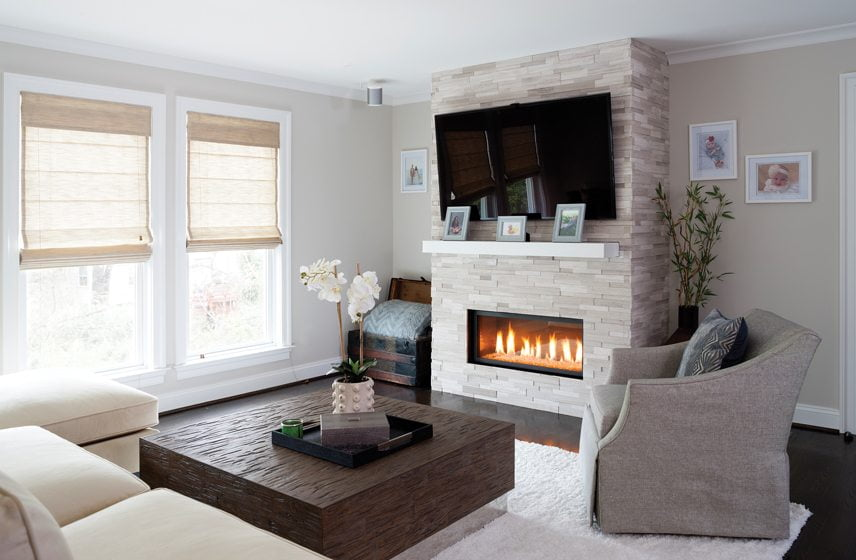 In the living room, the fireplace is now clad in white honed-ceramic tile.