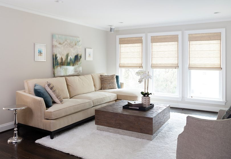 The living room features a rustic coffee table, sofa and swivel chair, all from Bernhardt.
