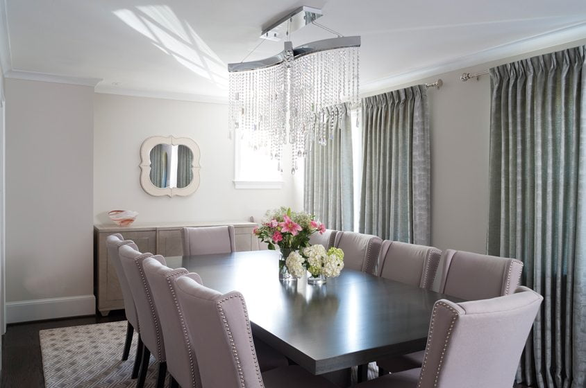 The dining room is adorned in light-neutral fabrics and finishes; the table is from Vanguard.