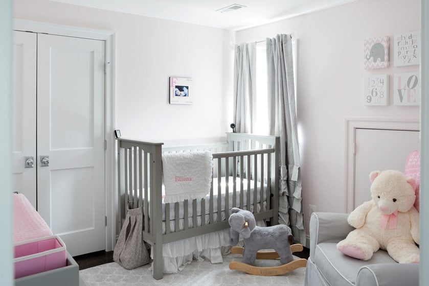 The nursery is a restful space with pale-pink walls and gray accents.