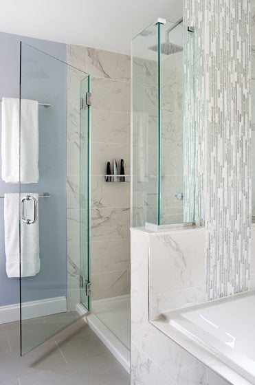 An intricate pattern of porcelain tile from Mosaic Tile adorns the shower enclosure.