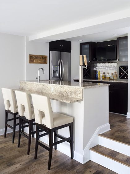 The lower level now features a recreation room with an adjoining kitchen and wet bar.