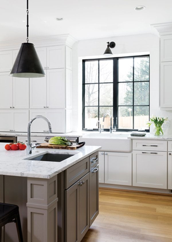 Marble surfaces and complementary light fixtures in both the kitchen and dining area further emphasize the black-and-white contrast.