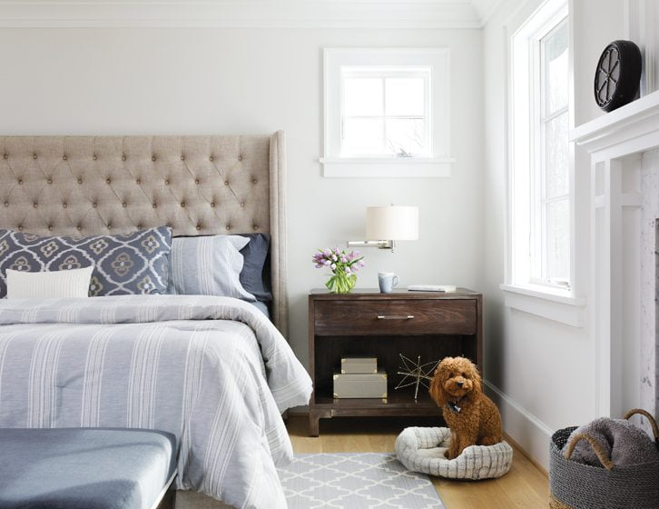 Fox left the window frames in the master bedroom white for a softer feel; a Restoration Hardware bedstead is a favorite perch for the couple's dogs—including their Cavapoo, Chewy.