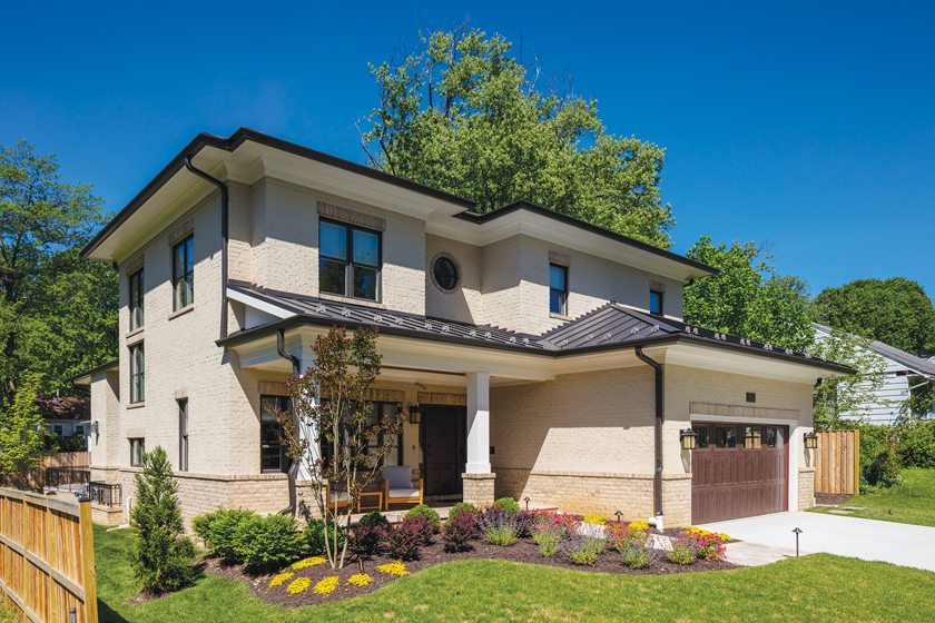 AV Architects + Builders designed this house in Falls Church, cladding it in brick veneer with a stucco-like coating.