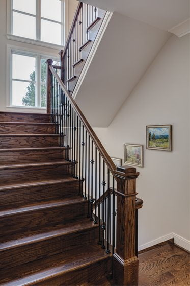 The dark-stained oak staircase leads up to two en suite bedrooms and down to a finished lower level.