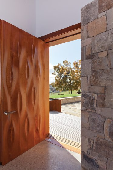 The front door sandwiches aircraft aluminum between expanses of hand-carved cedar on the exterior and walnut on the interior.