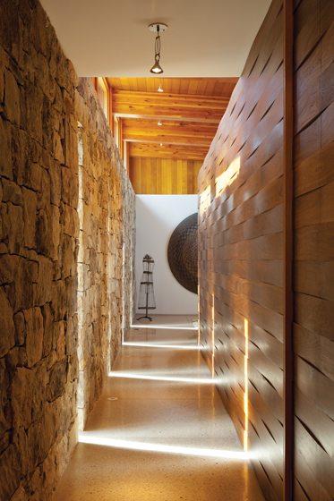 Sliver windows illuminate the long hallway, bordered on one side by walnut basket-weave paneling.