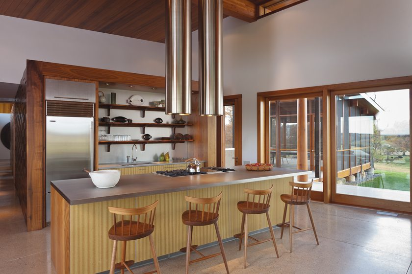 The kitchen island marries a sustainable-wood veneer with walnut end-caps. Burton designed the stainless-steel hood.