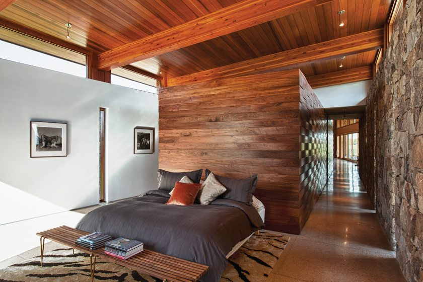 The master bedroom features a Hugh Acton walnut-and-brass bench.