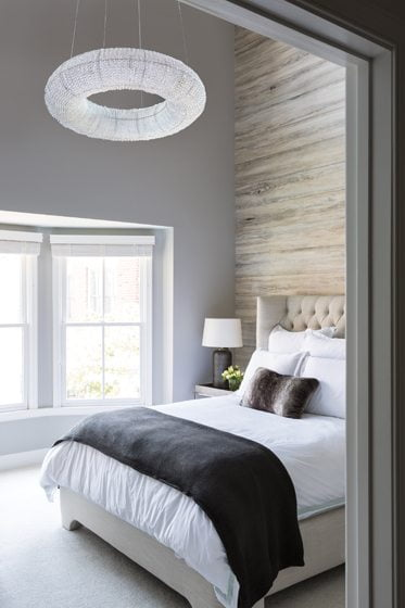 Walls painted Sherwin Williams Light French Gray create a serene backdrop in the master bedroom.