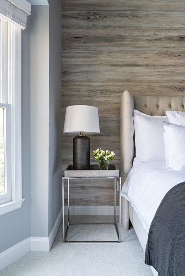 A wood-look wall covering by Stacey Tranter Artisan Wallpaper brings energy and a rustic vibe to the bedroom.