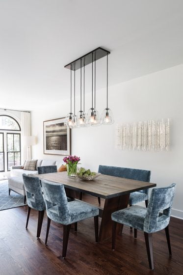 The custom dining table is paired with seating in Cowtan & Tout crushed velvet. The industrial-chic light fixture is from West Elm.