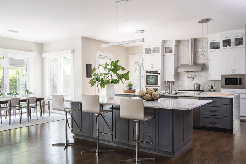 Maple cabinets in charcoal and white provide storage in the kitchen; quartz countertops and backsplash finish the look.