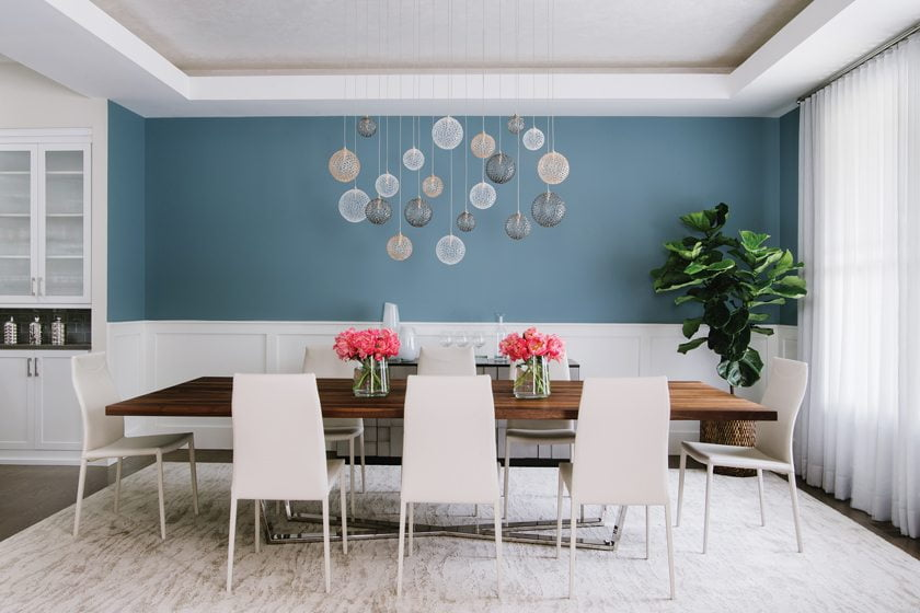 The dining room's hand-blown-glass light fixture by Shakuff is offset by walls painted in Benjamin Moore's Polaris.