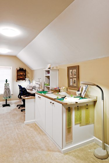 An L-shaped countertop features a sewing area while a higher surface is used for laying out fabrics. © Bob Narod