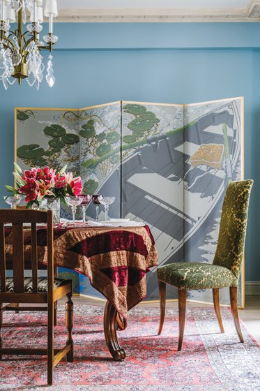 In the dining room, a painted screen by Jack Beal hides folding chairs and tables for large-scale entertaining.