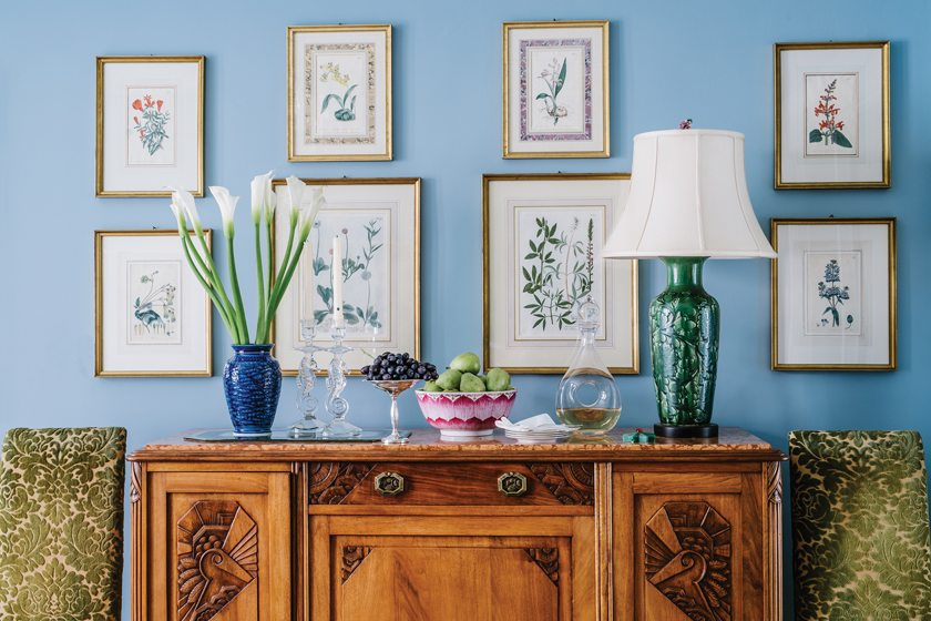A collection of inherited, hand-colored botanical prints is grouped over the dining room's Art Deco sideboard.