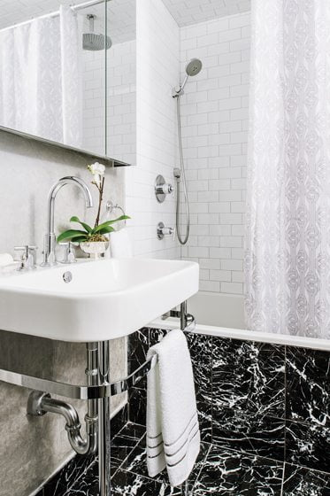 The classically styled, black-and-white marble bathroom boasts a sink with exposed plumbing by Duravit.