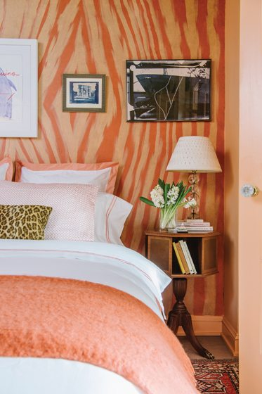In the bedroom, linens from Crane & Canopy complement faux bois stenciled walls in coral tones.