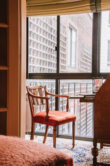 A small office area offers city views from a velvet-upholstered, circa-1930s chair from Scotland.