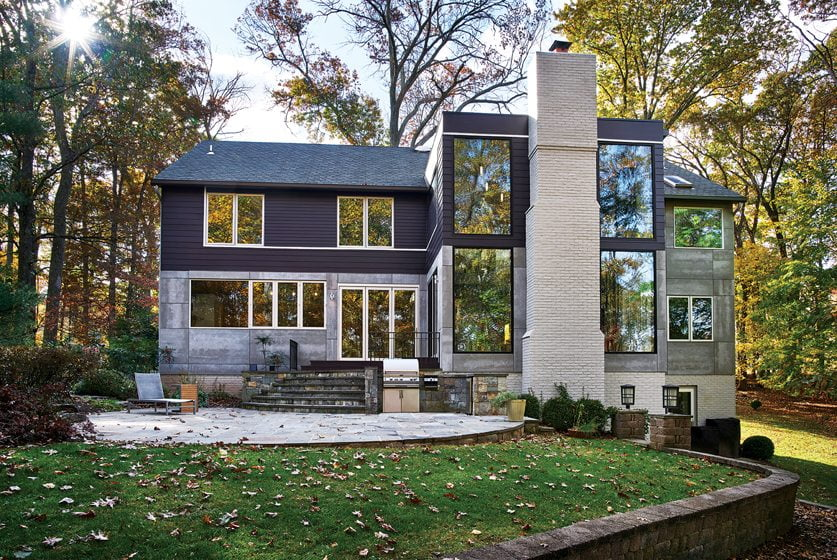 The back of the house boasts fiber-cement panels, large windows and glass doors.