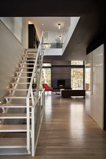 A new staircase with open risers and glass balustrades extends sight lines from the entry.