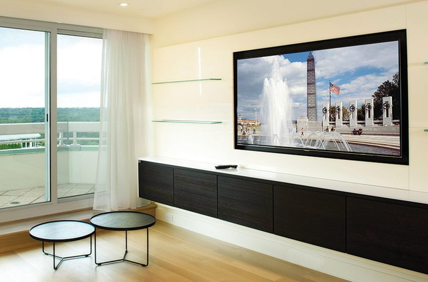 In a project by A.B.E. Networks, hidden A/V equipment controls a recessed Samsung TV via a universal remote. Five in-ceiling Sonance Architectural Speakers and an in-wall subwoofer deliver a surround-sound listening experience.