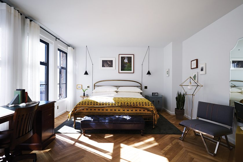 A brass bed frame and original artwork grace a District King room. Photo by Adrian Gaut