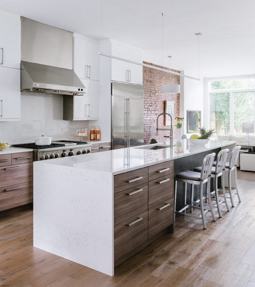 The kitchen island combines walnut lower cabinets and white quartz counters.