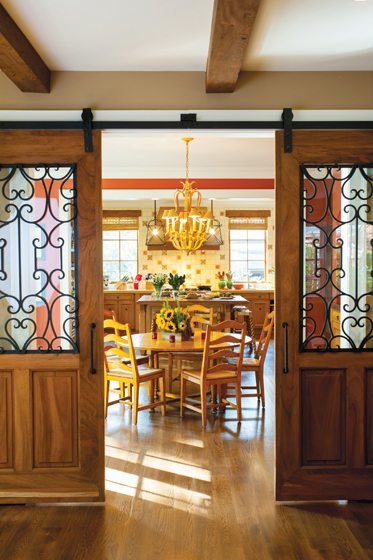Sliding doors with wrought-iron details made in Mexico lead to the kitchen.