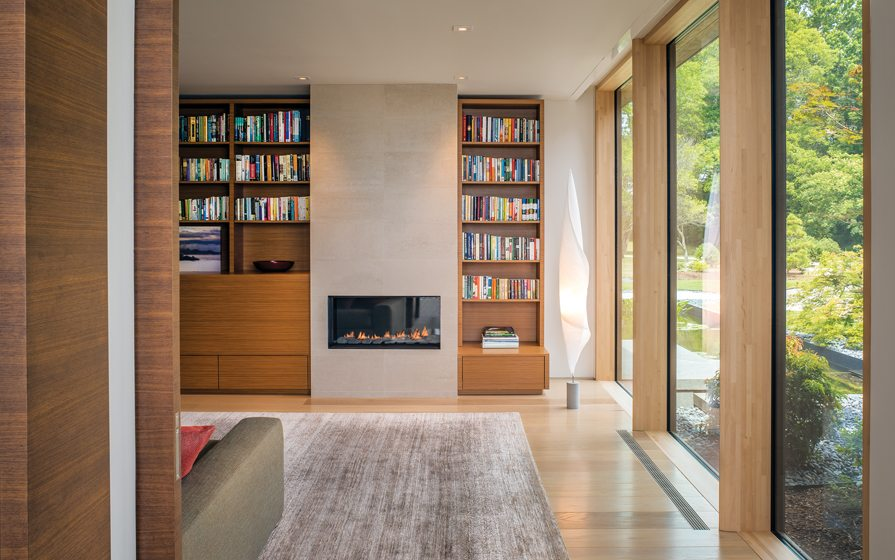 The den features teak built-ins and a Spark Modern fireplace.