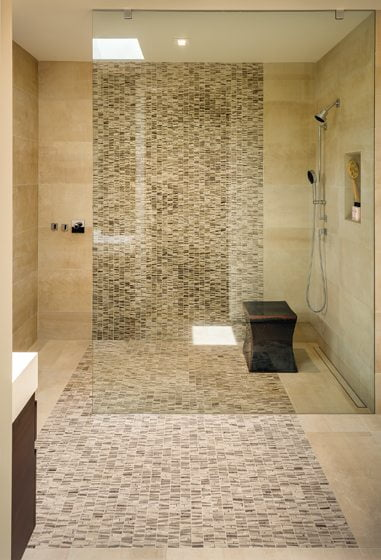 Twin master baths sport ribbons of Ann Sacks mosaic tile.