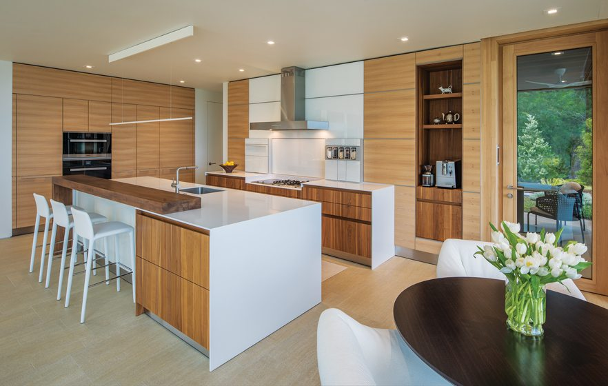 The sleek Bulthaup kitchen features warm wood cabinetry and quartz countertops.