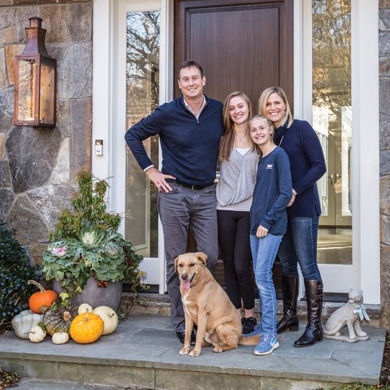 Scott and Jennifer Frederick pose at the front door with their daughters and rescue mutt, Wrigley.