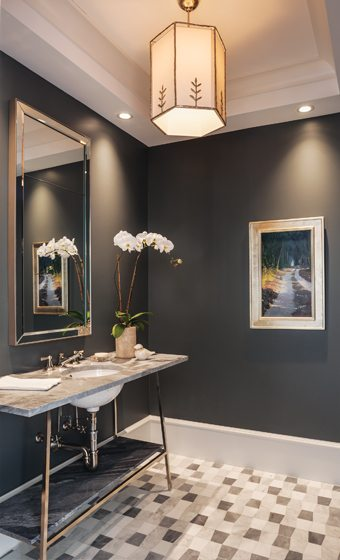 Walls painted in Farrow & Ball's Down Pipe add drama to the powder room.