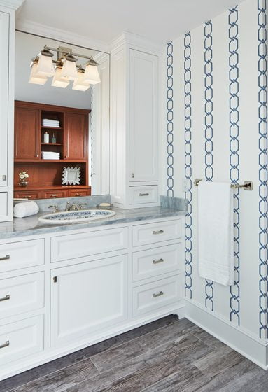 The master bath combines Lyndon Heath Cabinetry and wallpaper by Thibaut.
