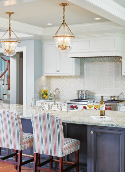Bar stools pull up to the kitchen island, topped by granite from Atlas Stone.