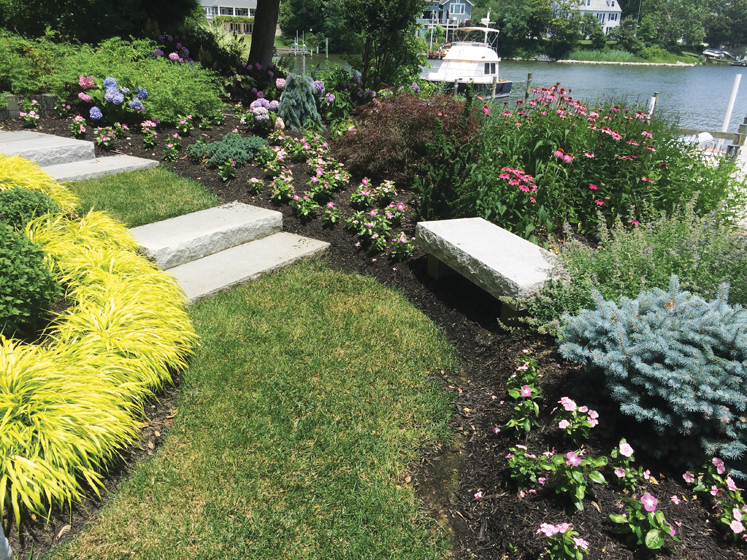 A waterfront project installed by Vista Pro features a bench positioned to take in the garden. © James Landot