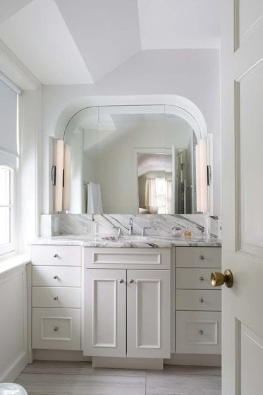 The classically styled master bath combines marble and white cabinetry.