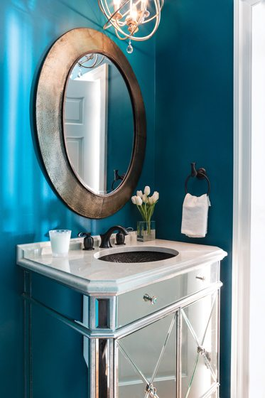 The powder room is painted vibrant blue.