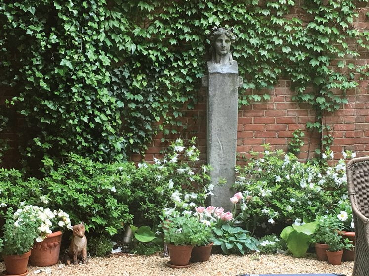 A stone sculpture extends the classical mood to the terrace.