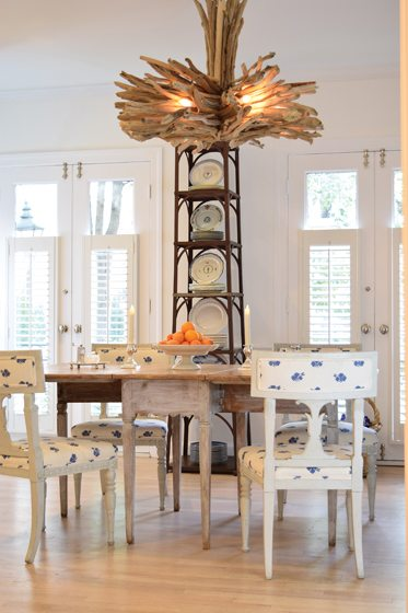 A driftwood chandelier from Mexico hangs above a Swedish gate leg table.