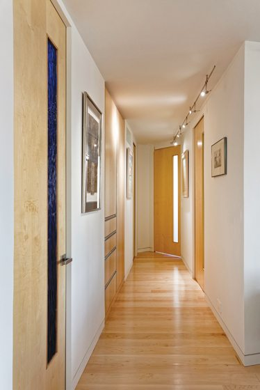A hallway reveals custom pocket doors and built-in storage.