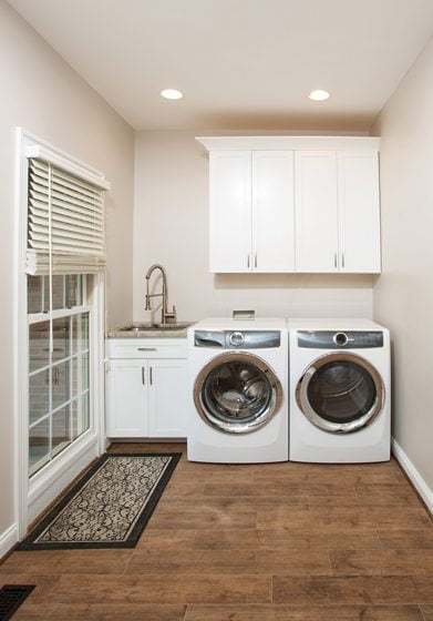 The laundry area features built-ins and a sink.